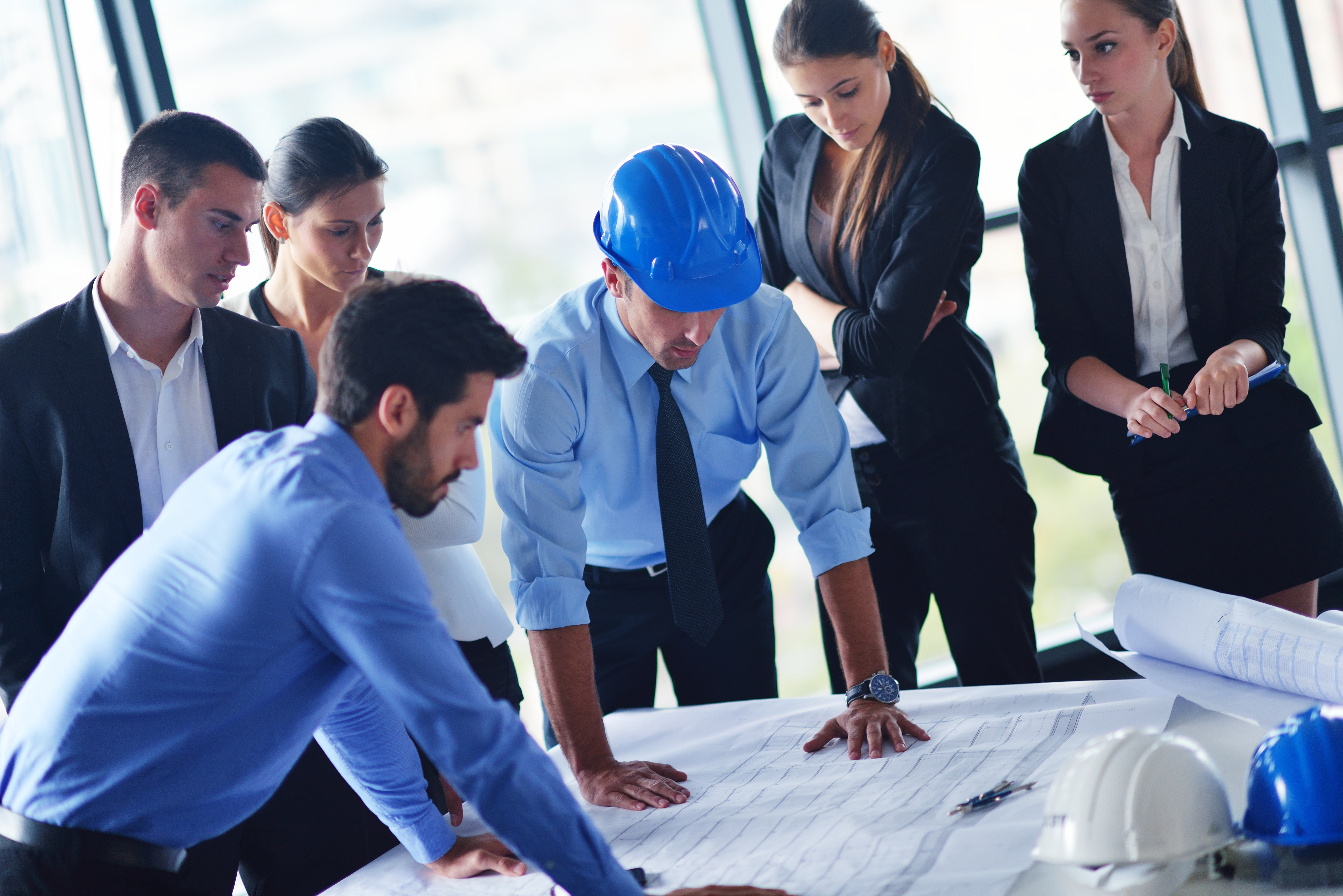 Six people stand and look at blueprints on a table. One man is wearing a hard hat.