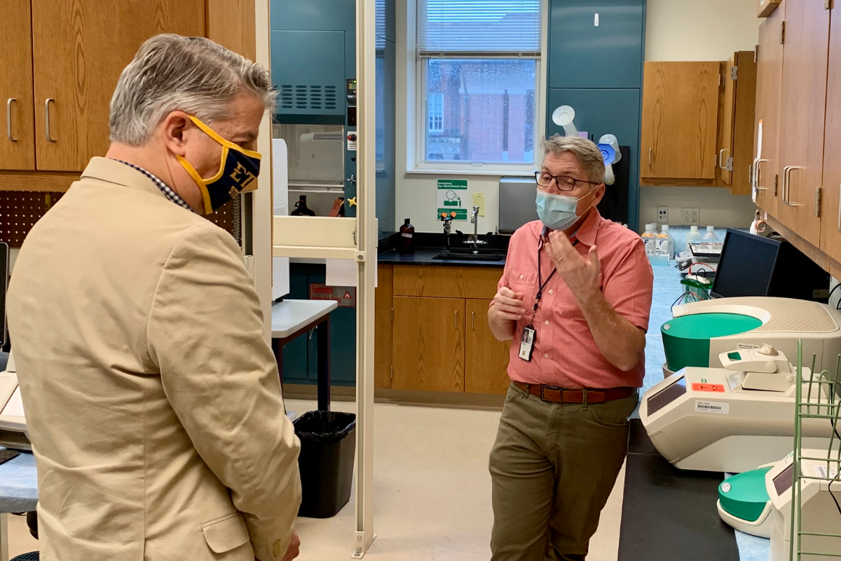 Two men, David Golden and Jon Moorman, talk in a science laboratory.