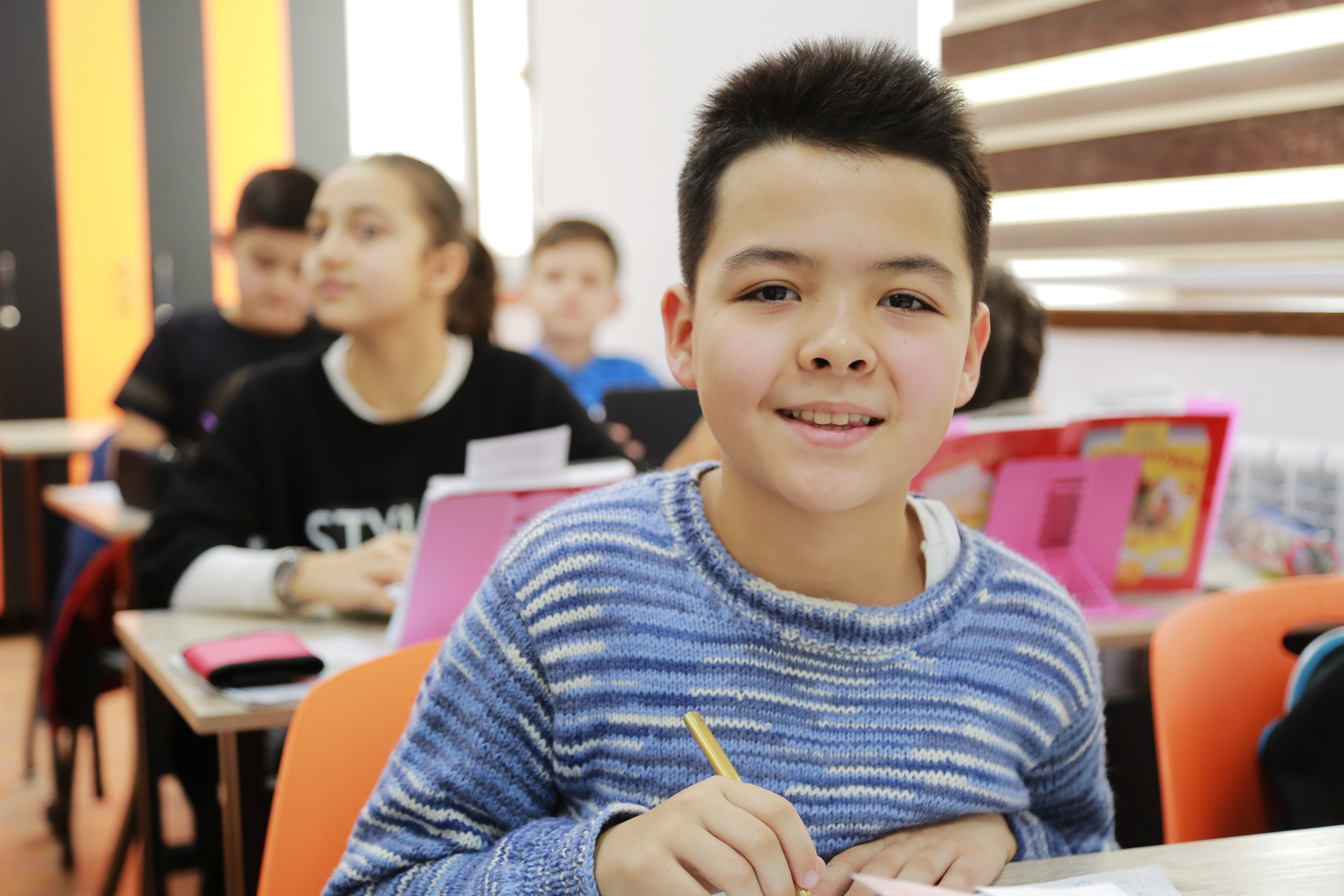 Little boy smiling and holding a pencil to paper at a classroom desk.