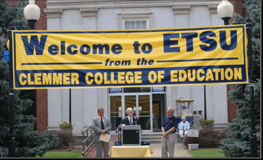 Three men from Clemmer College stand outside Warf Pickel Hall on the main campus under a sign that says welcome to ETSU from the Clemmer college.