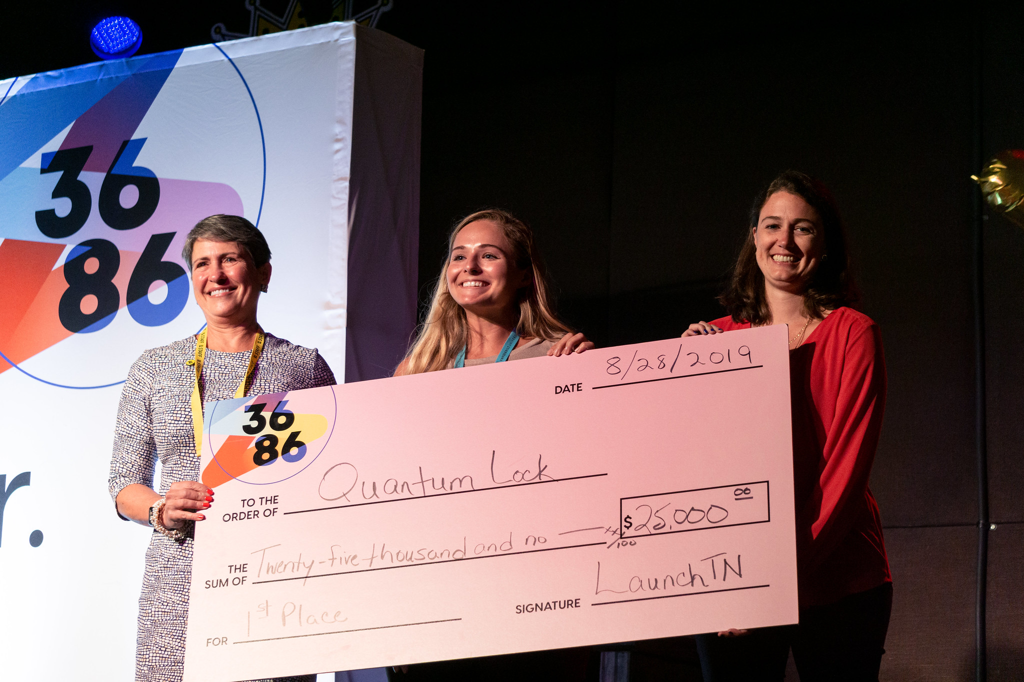 Three women hold a large check for Quantum Lock. The check is signed by Launch Tennessee.