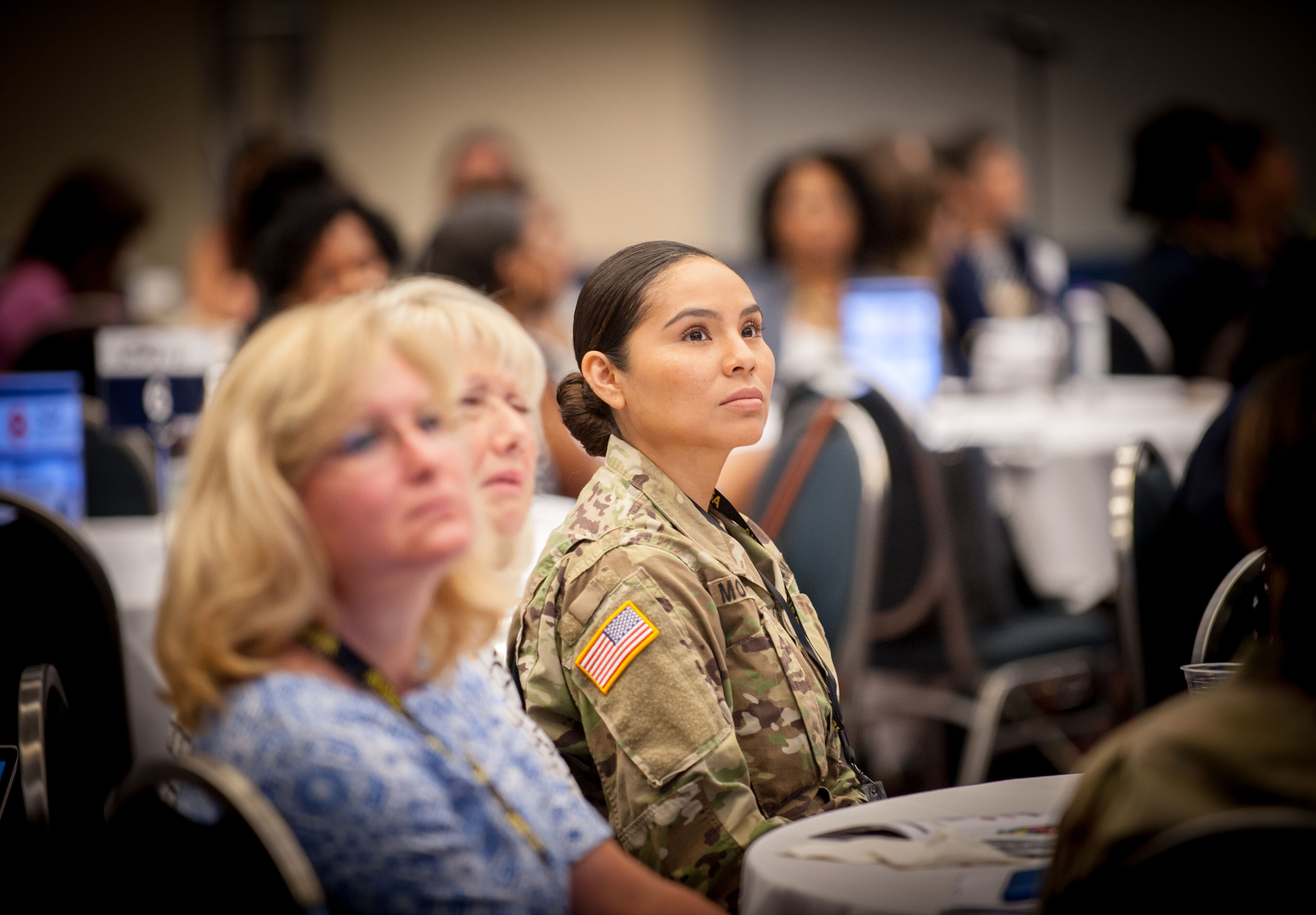 Woman in camouflage sits in a seminar room.