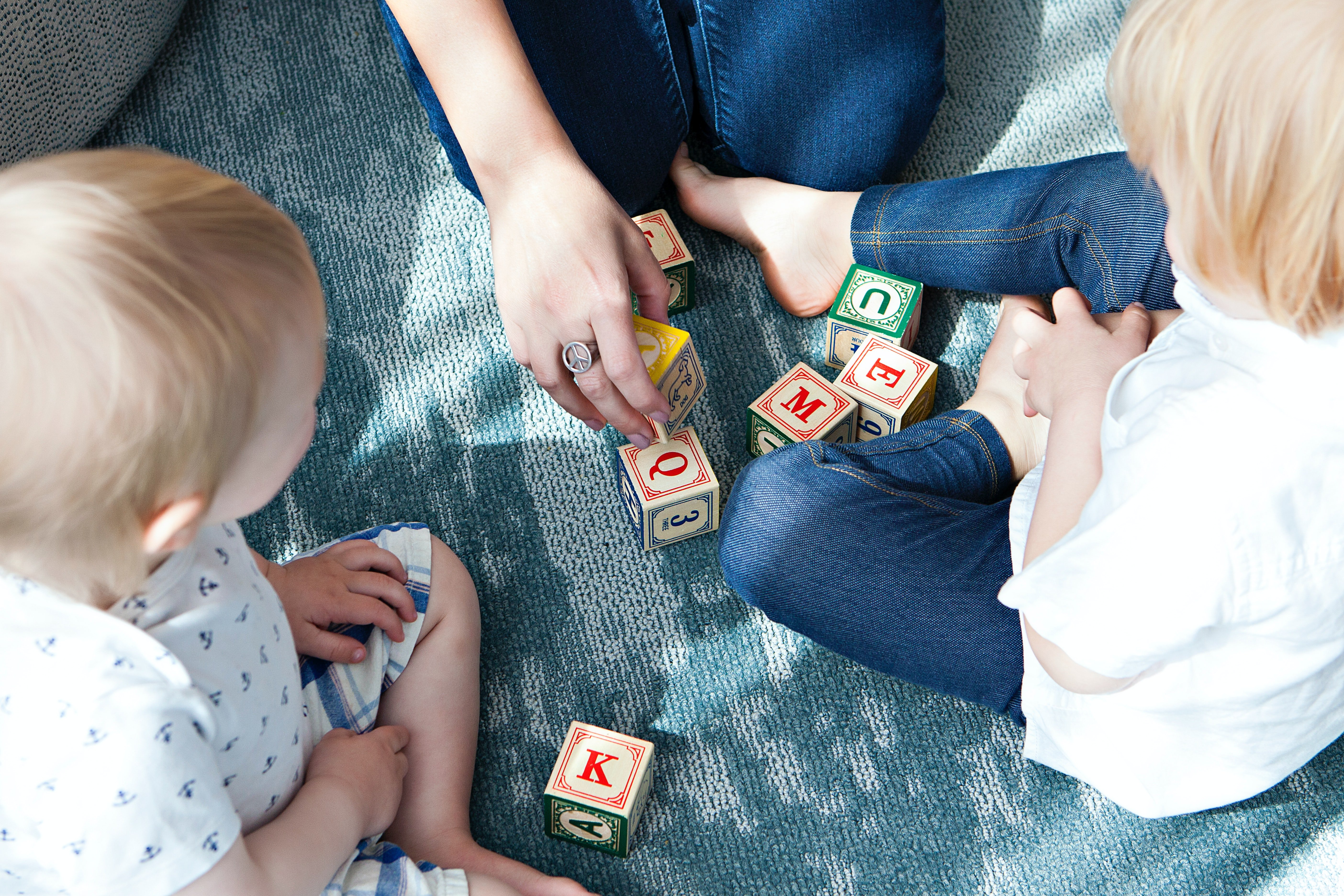 Two little kids and an adult playing with alphabet blocks.