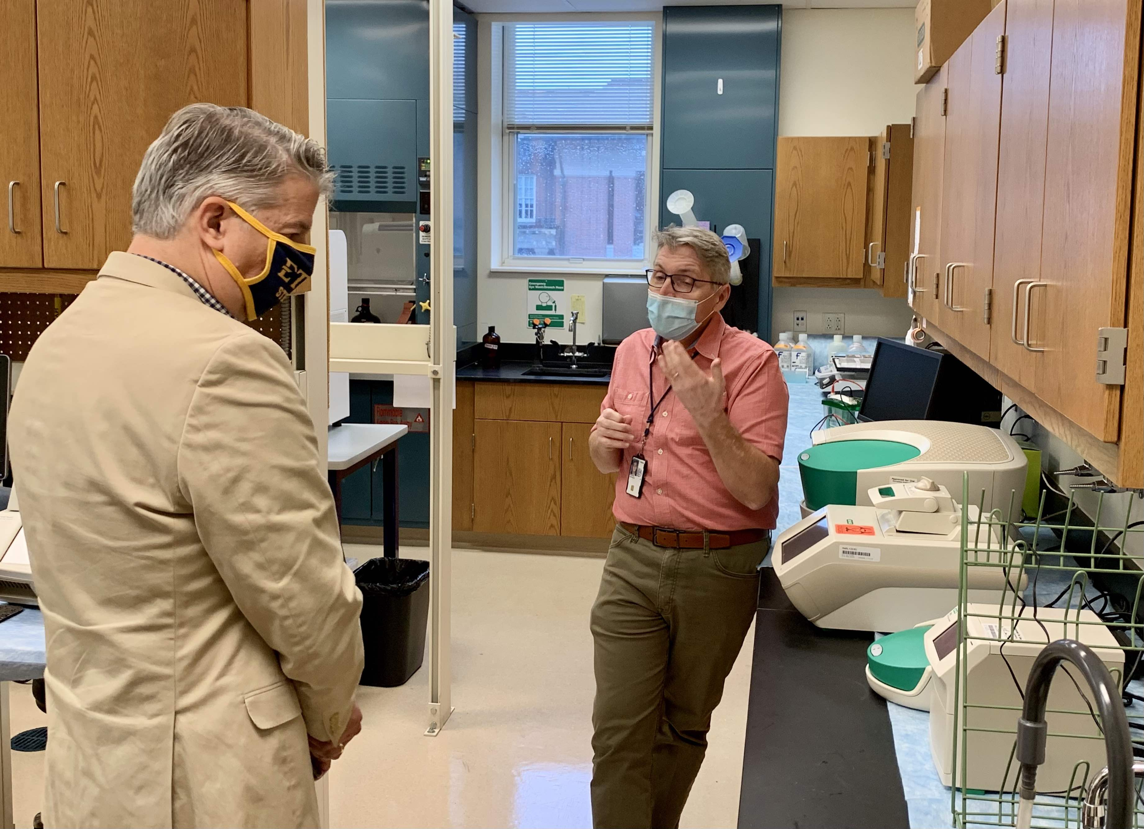 Two men, Jon Moorman and David Golden, talk in a laboratory of science equipment.